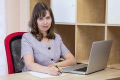 Ung kvinna med en bärbar dator fotografering för bildbyråer