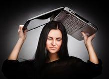 Ung kvinna med en bärbar dator på henne som är head Arkivfoton