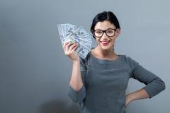 Ung kvinna med en bunt av kontanta USD fotografering för bildbyråer