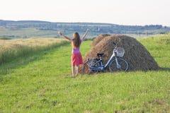 Ung kvinna med en cykel på fält med höstackar på en solig da royaltyfri fotografi