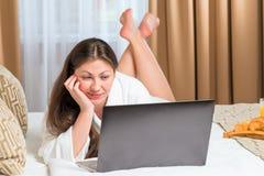 Ung kvinna med en dator på sängen Arkivfoto