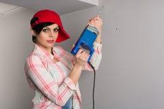 Ung kvinna med en gammal byggmästare med drillborren arkivbilder