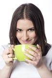 Ung kvinna med en grön kopp Arkivfoton