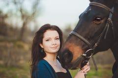 Ung kvinna med en häst på naturen Royaltyfri Fotografi
