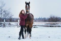 Ung kvinna med en häst på naturen i vinter på snö royaltyfria bilder
