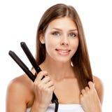 Ung kvinna med en hårstraightener Royaltyfria Bilder