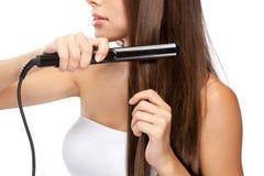 Ung kvinna med en hårstraightener Royaltyfri Foto