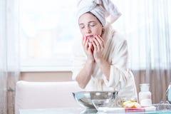 Ung kvinna med en handduk på hennes huvud som tvättar hennes framsida med vatten i morgonen Hygien och omsorg för huden arkivfoto