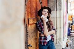 Ung kvinna med en hatt bredvid en gammal trädörr arkivfoto