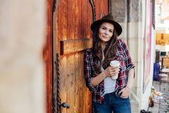 Ung kvinna med en hatt bredvid en gammal trädörr royaltyfri fotografi