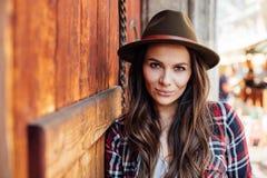 Ung kvinna med en hatt bredvid en gammal trädörr arkivbild