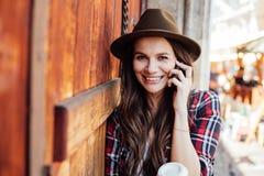 Ung kvinna med en hatt bredvid en gammal trädörr som talar på cel royaltyfria bilder