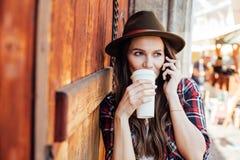 Ung kvinna med en hatt bredvid en gammal trädörr som talar på cel royaltyfri foto
