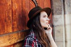 Ung kvinna med en hatt bredvid en gammal trädörr som talar på cel royaltyfria foton