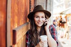 Ung kvinna med en hatt bredvid en gammal trädörr som talar på cel arkivfoto