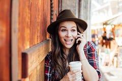 Ung kvinna med en hatt bredvid en gammal trädörr som talar på cel royaltyfri fotografi