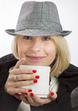 Ung kvinna med en hatt och en vit kopp arkivbild