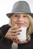 Ung kvinna med en hatt och en vit kopp royaltyfria foton