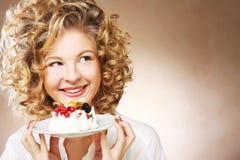 Ung kvinna med en kaka arkivbild