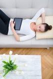 Ung kvinna med en minnestavlaPC på soffan Royaltyfria Foton