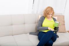 Ung kvinna med en minnestavlaPC på soffan arkivfoto