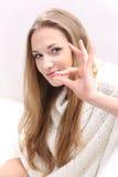 Ung kvinna med en pill Royaltyfria Bilder