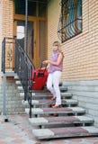 Ung kvinna med en röd resväska Arkivfoto
