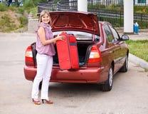 Ung kvinna med en röd resväska i bilen Arkivbild