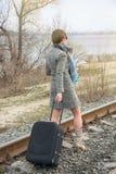 Ung kvinna med en resväska och en kamera på stängerna royaltyfri fotografi