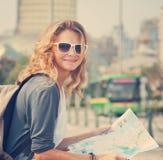 Ung kvinna med en stadsöversikt och en ryggsäck royaltyfria foton