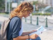 Ung kvinna med en stadsöversikt och en ryggsäck Arkivfoton