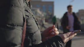 Ung kvinna med en telefon på en upptagen gata arkivfilmer