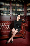 Ung kvinna med ett exponeringsglas av konjak Fotografering för Bildbyråer