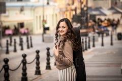 Ung kvinna med ett fiolfall som ler againgt en gata arkivfoton