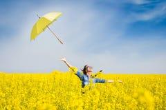 Ung kvinna med ett paraply i canolafält Fotografering för Bildbyråer