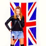 Ung kvinna med exponeringsglas av alkohol som står över den Union Jack flaggan Royaltyfria Bilder