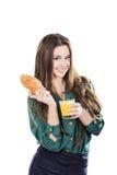 Ung kvinna med exponeringsglas av fruktsaft och gifflet Royaltyfria Foton