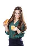 Ung kvinna med exponeringsglas av fruktsaft och gifflet Arkivbild