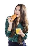 Ung kvinna med exponeringsglas av fruktsaft och gifflet Arkivfoto