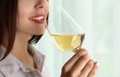 Ung kvinna med exponeringsglas av lyxigt vitt vin inomhus, closeup arkivfoto