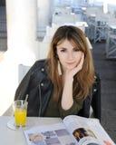 Ung kvinna med exponeringsglas av orange fruktsaft och tidskriften Arkivbilder