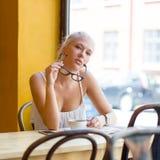 Ung kvinna med exponeringsglas på kafét Arkivbild