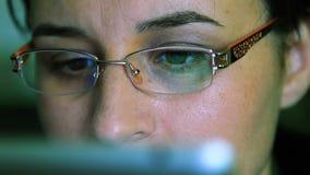 Ung kvinna med exponeringsglasarbete på en minnestavladator lager videofilmer