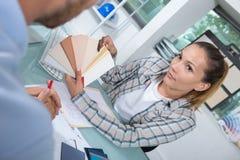 Ung kvinna med färgprovkartor eller prövkopior som visar till kunden arkivfoton