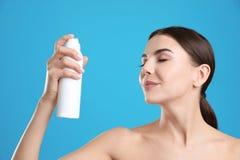 Ung kvinna med flaskan av termiskt vatten på färgbakgrund arkivfoto