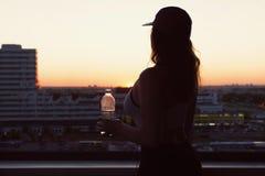 Ung kvinna med flaskvatten, når att ha joggat på solnedgångbakgrunderna Bästa sikt på staden Royaltyfria Bilder