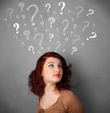 Ung kvinna med frågefläckar ovanför hennes huvud Arkivbilder