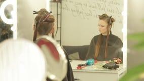 Ung kvinna med gemet för att fixa långt hår under friseringsammanträde i stolframdelspegel i skönhetstudio Kvinna stock video