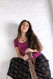 Ung kvinna med gitarren i lång kjol vägg för rastre för bakgrundstegelstenbild Royaltyfria Bilder