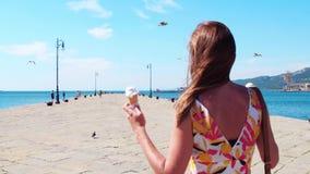 Ung kvinna med glasskottar som går på havspir Arkivfoton